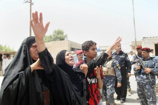 Des familles pleurent les victimes de l'attentat à... (Photo: AFP)