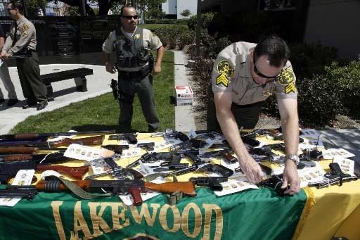 Un policier dispose des armes confisquées aux inculpés.... (Photo AP)