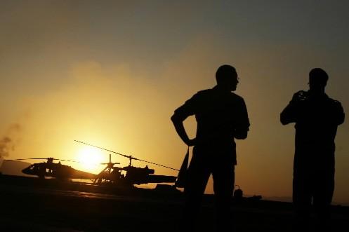 Deux soldats devant un hélicoptère de l'OTAN au... (Photo: Reuters)