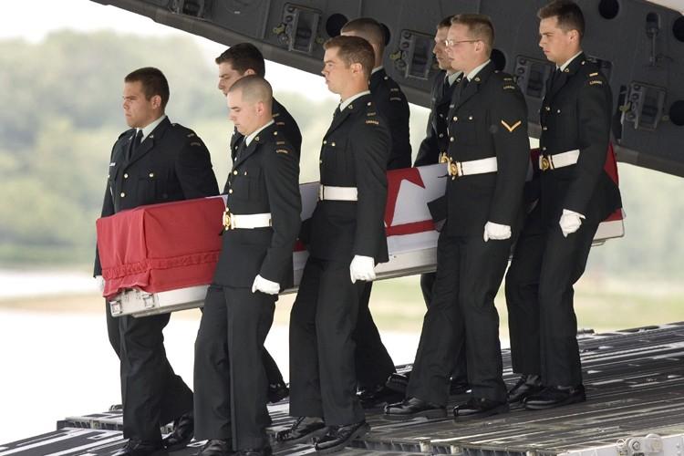Un avion militaire transportant le cercueil du caporal... (Photo: Reuters)
