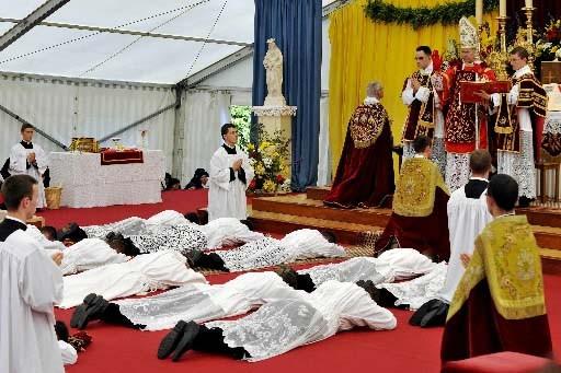 Les nouveaux prêtres se prosternent devant l'évêque Bernard... (Photo AFP)