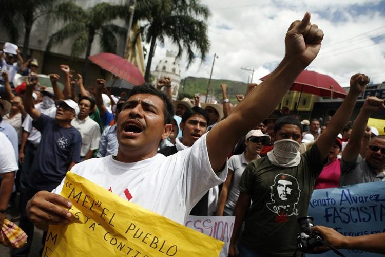 Des supporters de Manuel Zelaya chantent l'hymne national... (Photo: Reuters)