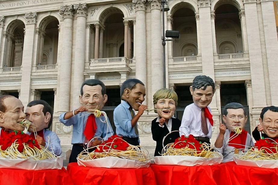 Des militants de l'organisation Oxfam portent des masques... (Photo: Reuters)