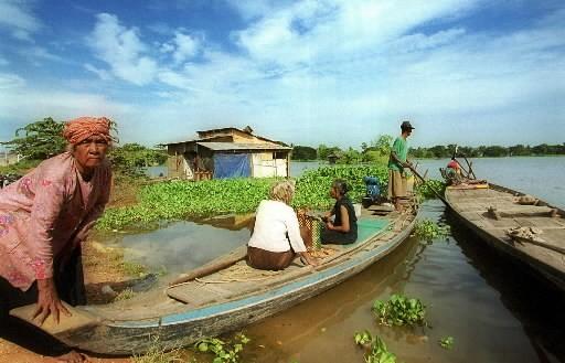 Des Cambodgiens montent à bord de petits bateaux... (Photo AP)