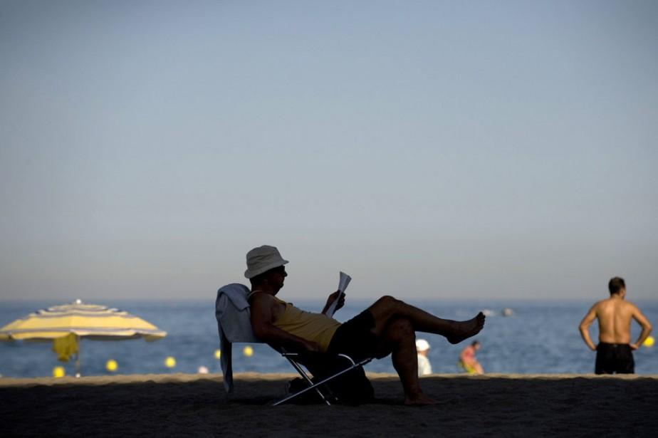 Un touriste lit sur la plage à Torremolinos.... (Photo: AFP)