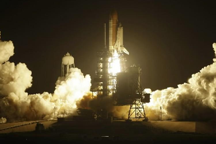 La navette Discovery au moment de son décollage,... (Photo: AP)