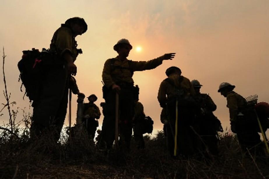 Il faudra encore des semaines aux pompiers avant... (Photo AFP)