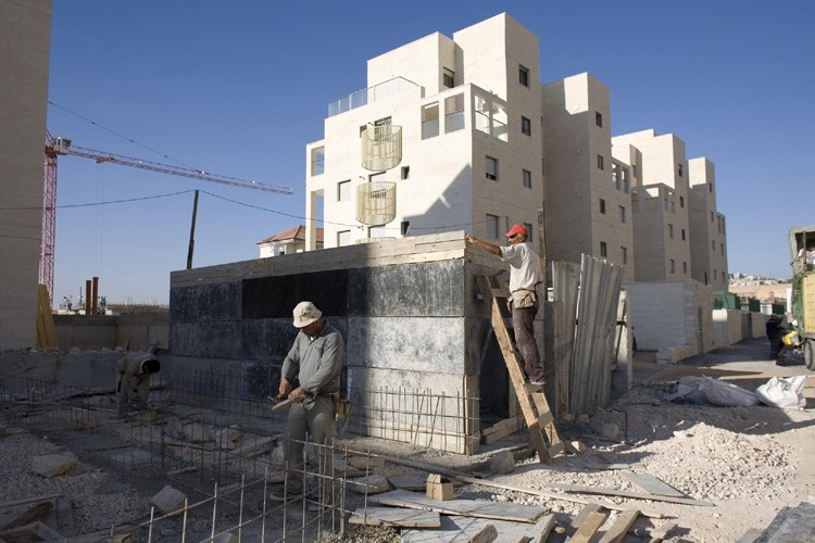Des employés palestiniens construisent de nouveaux logements dans... (Photo: AP)
