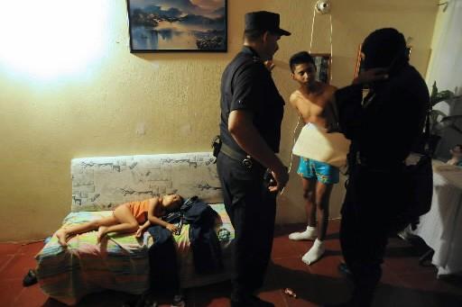 Les policiers arrêtent un membre présumé du gang,... (Photo AFP)