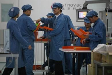 Des travailleurs chinois inspectent des échantillons du premier... (Photo AP)