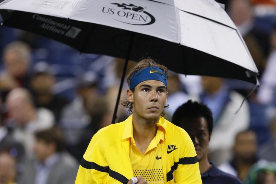 Rafael Nadal se protège de la pluie.... (Photo: Reuters)