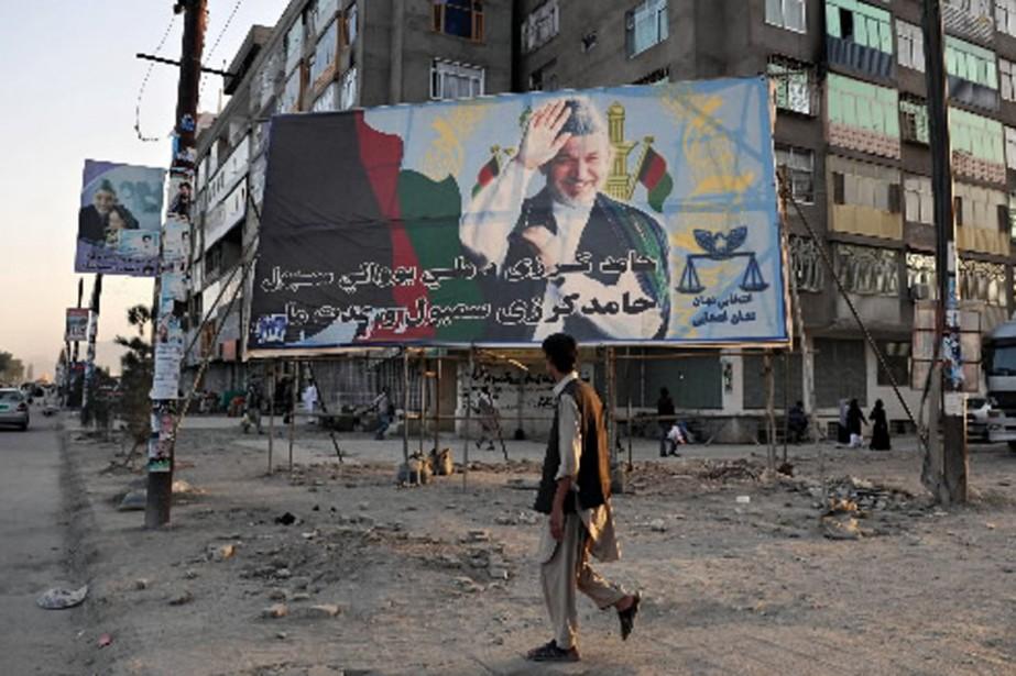 Un homme marche devant une affiche électorale d'Hamid... (Photo AFP)