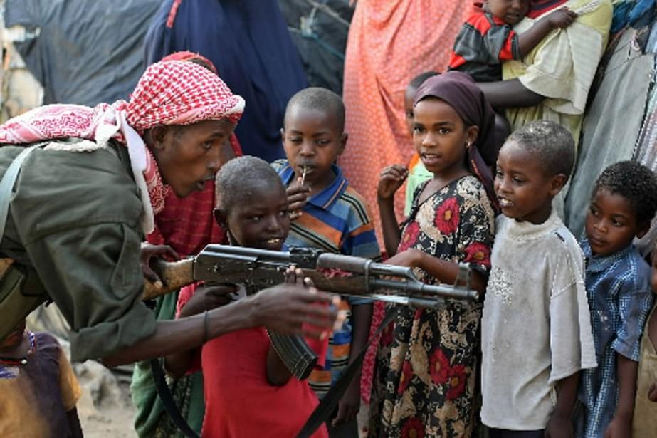 Un soldat somalien explique à un enfant comment... (Photo AFP)