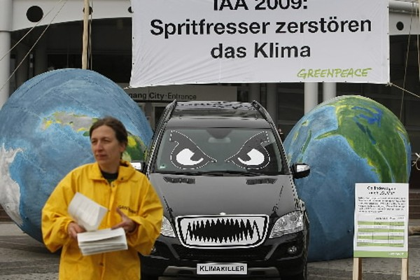 Une membre du groupe Greenpeace distribue des pamphlets... (Photo: AP)