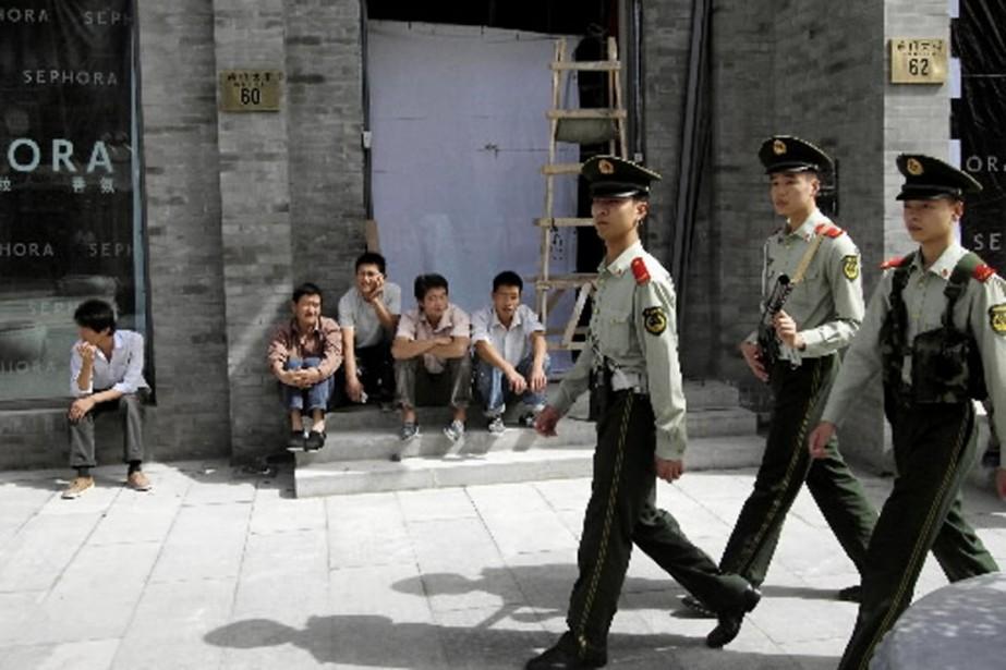 Des policiers patrouillent près de la place Tiananmen,... (Photo AP)