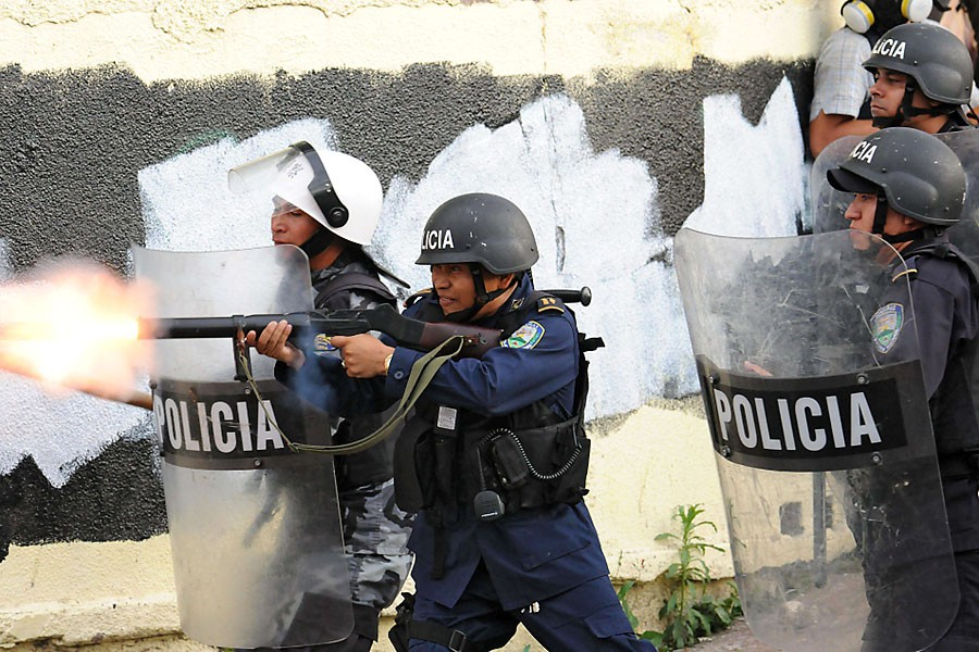 Des membres de l'escouade antiémeutes tentent de repousser... (Photo  AFP)