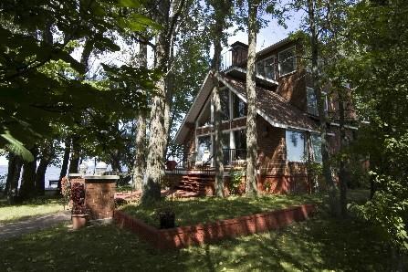 La maison sur l'île est entourée d'arbres...et d'eau!...