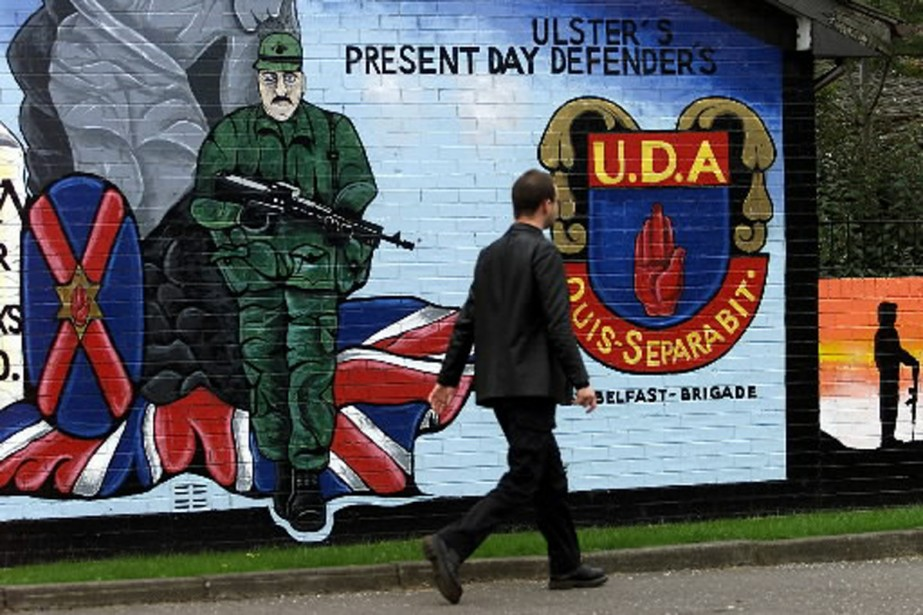 Un homme marche devant une affiche de la... (Photo archives AP)