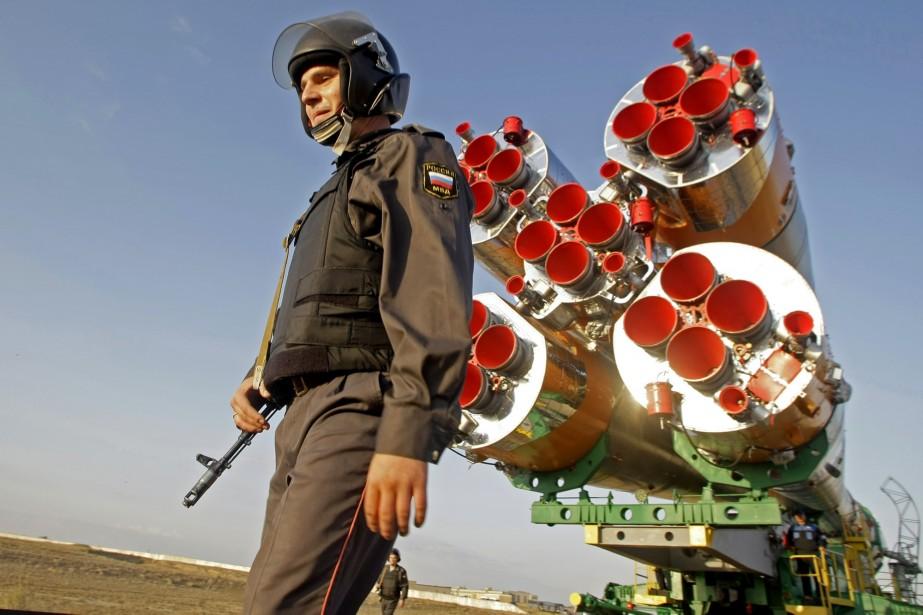 Un policier russe surveille la fusée Soyouz.... (Photo: AP)
