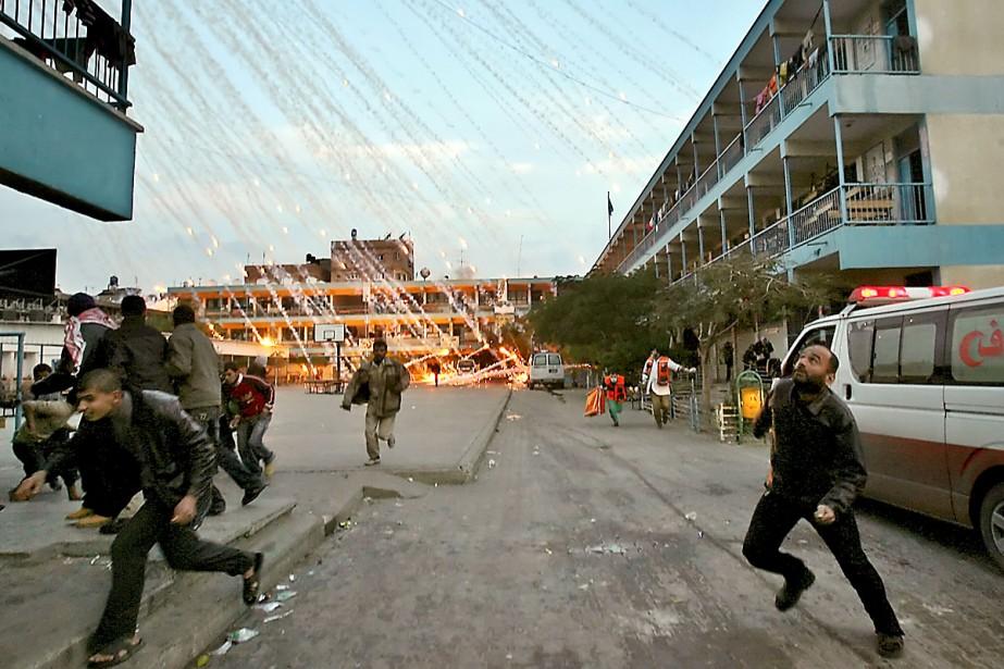 Des civils et des ambulanciers palestiniens courent se... (Photo AFP)