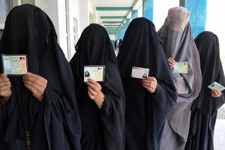 Des Afghanes présentent leurs cartes d'identité avant de... (Photo: AFP)