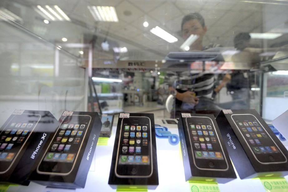 Une vendeuse derrière un présentoir de téléphones à... (AFP)