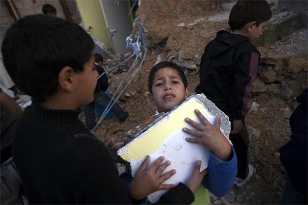 Un garçon palestinien transporte des débris de sa... (Photo: AFP)