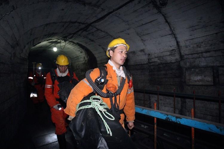 Des sauveteurs cheminent dans un tunnel de la... (Photo AP)