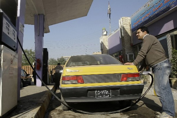 Un automobiliste fait le plein à une station... (Photo: Mohammed Ameen, Reuters)