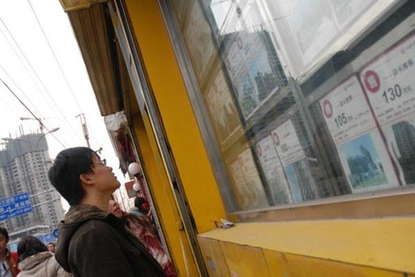Un chinois regarde des publicités de maisons à... (Photo: AFP)