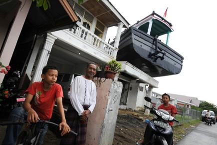 Des survivants du tsunami posent devant le bateau... (Photo: Romeo Gacad, AFP)