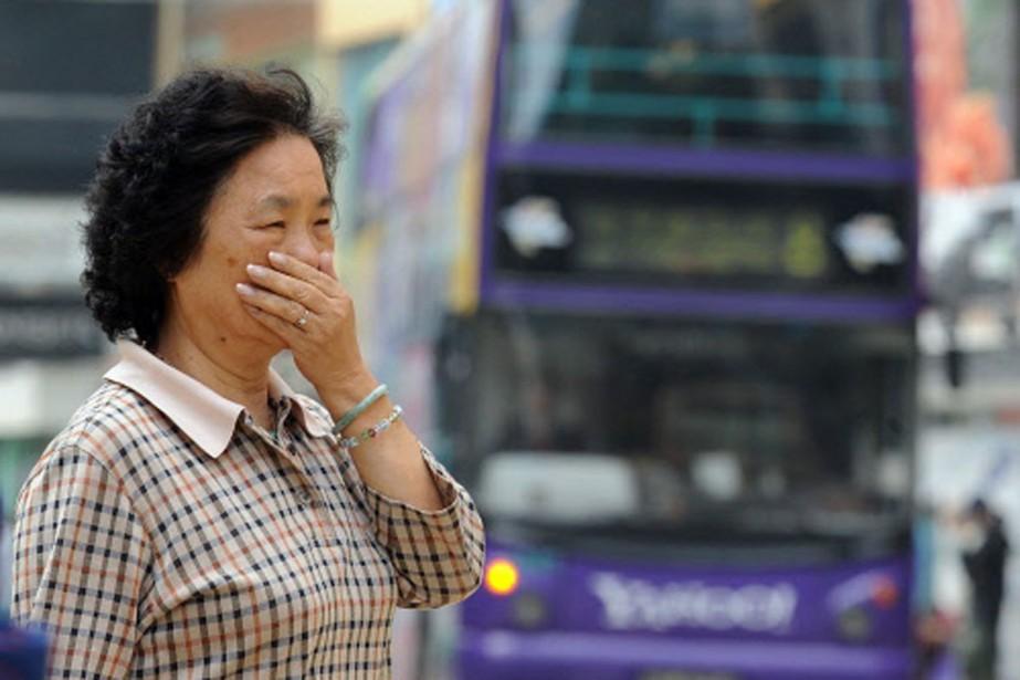 Une femme se couvre le visage pour marcher... (Photo: AFP)