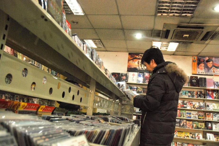 Un jeune Chinois dans un magasin de DVD... (Photo: AFP)