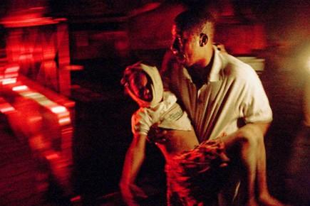Un homme transporte un enfant blessé près de... (Photo: Ivanoh Demers, La Presse)