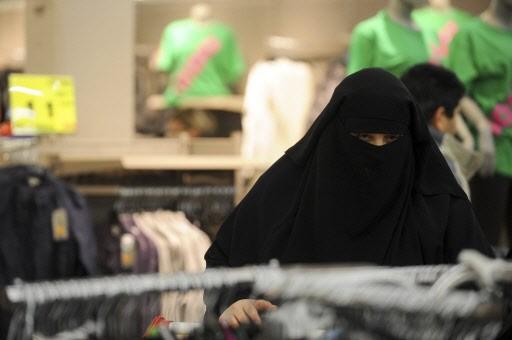 Une femme portant le niqab fait les boutiques... (Photo: Reuters)