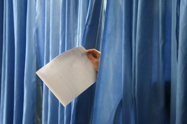 Une femme quitte son isoloir avec son bulletin... (Photo: Reuters)