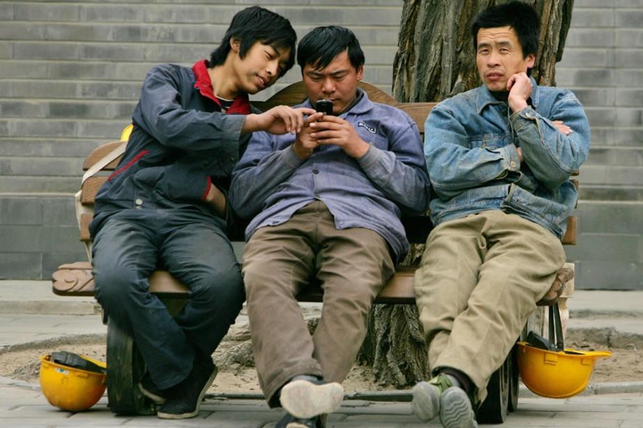 Des travailleurs chinois utilisent un téléphone cellulaire... (Photo: AP)