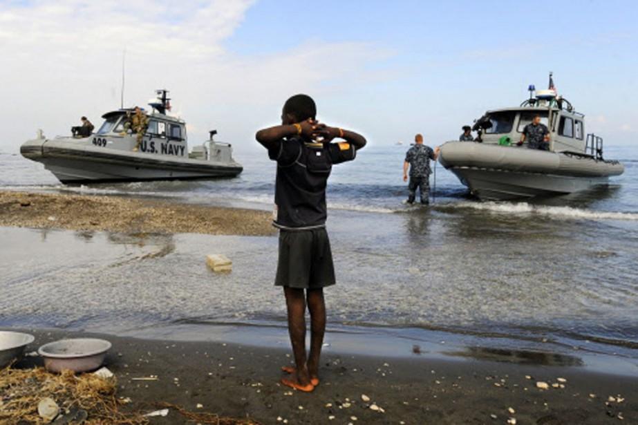 Un jeune haïtien observe les secours américains débarquer... (Photo: AP)