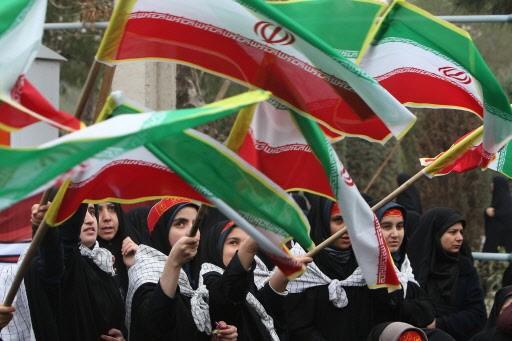 Des étudiantes de Qom agitent le drapeau iranien... (Photo: AFP)