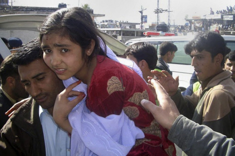 Terrorisée, une jeune fille est évacuée des environs... (Photo: Reuters)