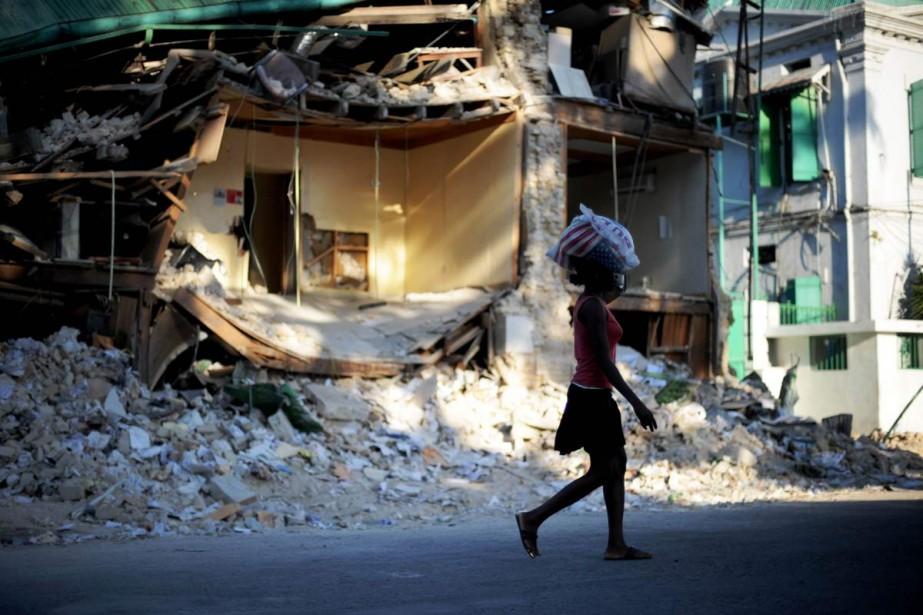 À Port-au-Prince, une femme transporte un sac de... (Photo AFP)