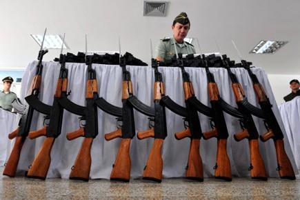 Un policier colombien dispose des Ak-47 saisis dans... (Photo: Luis Robayo, AFP)