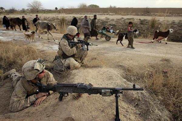 Des civils afghans marchent à proximité de soldats... (Photo Reuters)