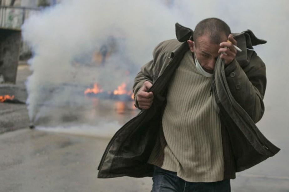 Un Palestinien fuit les gaz lacrymogènes lancés par... (Photo: AP)