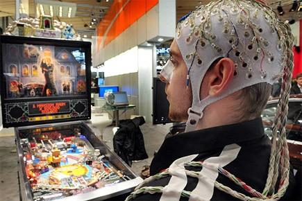 Un cobaye arborant un bonnet couvert d'électrodes actionne... (Photo: AFP)