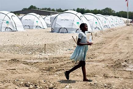 Une jeune fille marche devant un campement de... (Photo: Sophia Paris, archives Reuters)