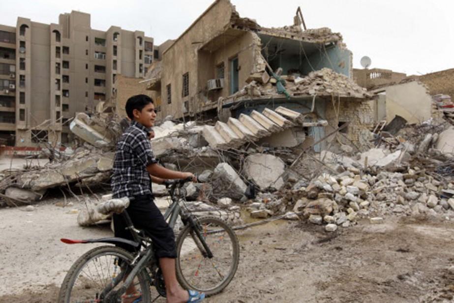 Un jeune garçon regarde les dégâts causés par... (Photo: AP)