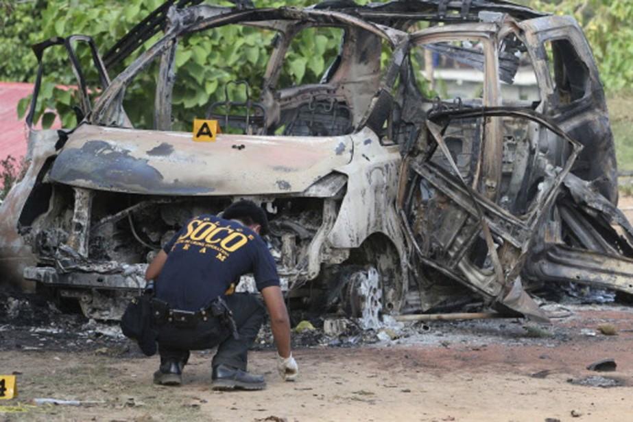 Un policier récolte des indices sur les lieux... (Photo: Reuters)