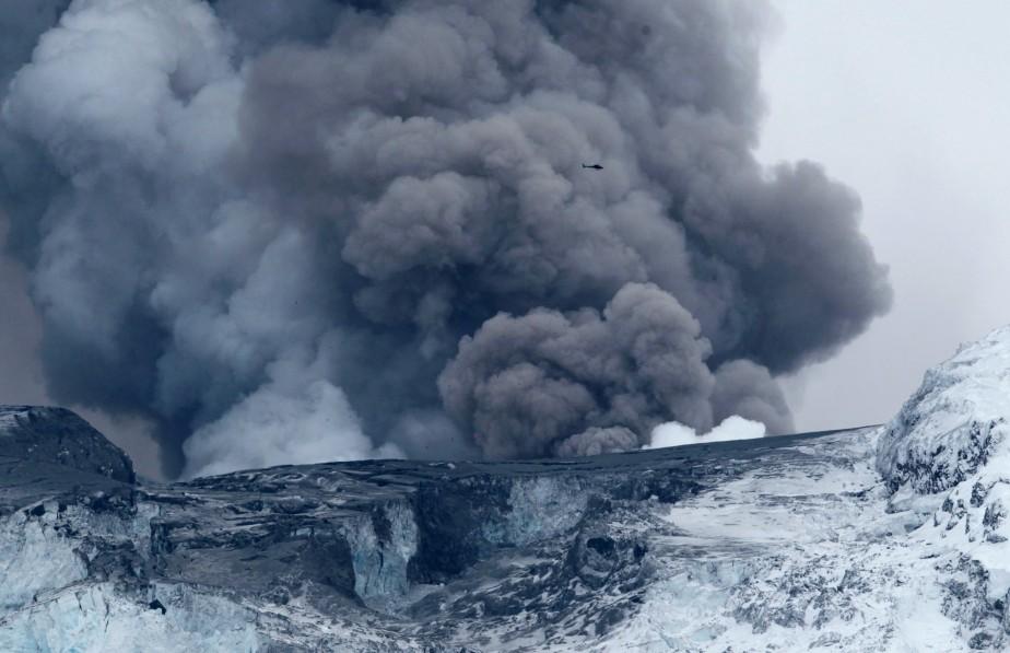 Un hélicoptère survole le volcan Eyjafjallajokull, qui continue... (PHOTO: LUCAS JACKSON, REUTERS)