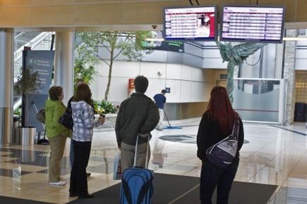 Des passagers surveillent le tableau des vols en... (Photo PC)